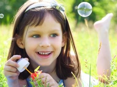 Nena sonrient i fent bombolles