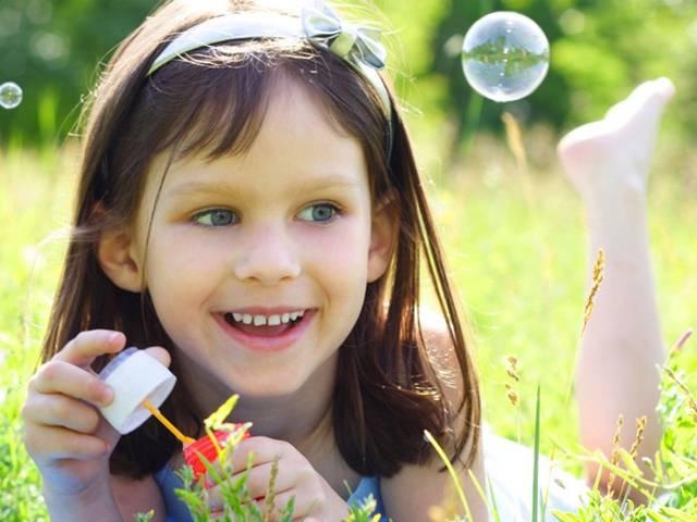Niña sonriendo y haciendo burbujas