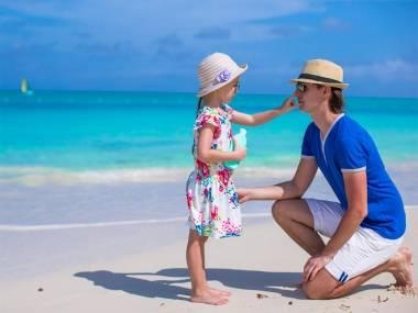 Nena aplicant crema solar al seu pare a la platja