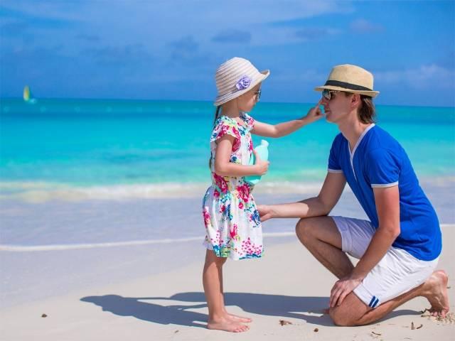 Niña aplicando crema solar a su padre en la playa