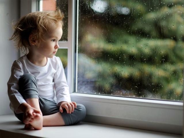 Nen mirant a la finestra en un dia de pluja