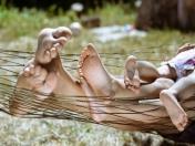 Pies de una familia tumbada en una hamaca