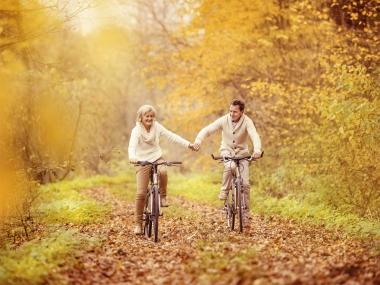 Pareja senior paseando en bicicleta otoño