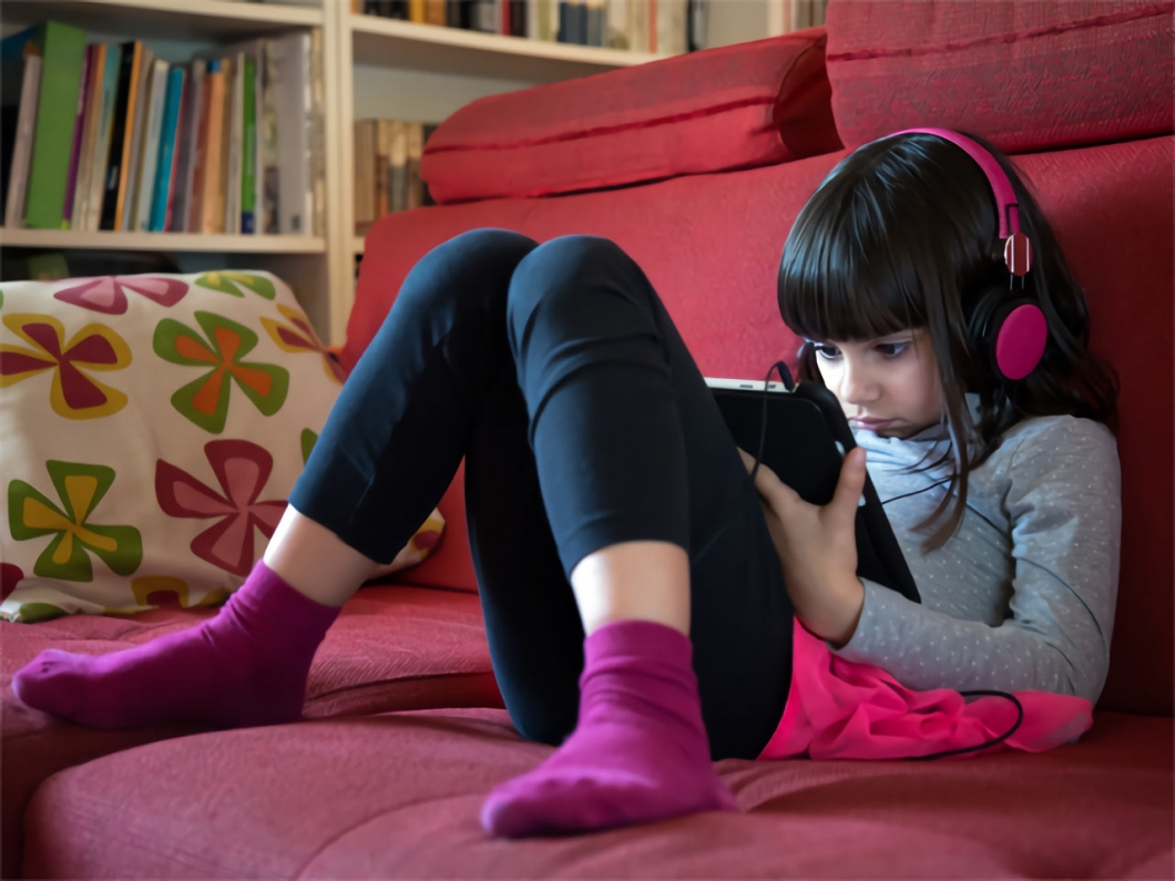 Nena amb tauleta al sofa